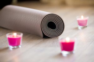 Rose-colored lighted pink wax candle and rolled brown yoga pilates mat on the floor
